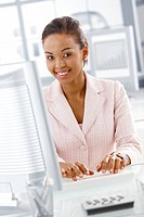 Portrait of smiling businesswoman sitting at desk, working on computer, looking at camera.