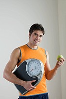 Sportsman holding scale and apple, concept: healthy lifestyle