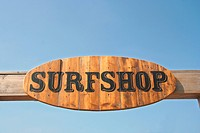 Wooden sign at the beach saying Surfshop