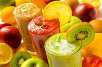 Three orange, red and green smoothies with colorful fruits in the background.