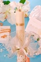 white candle with decoration for first holy communion on blue background