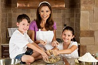 An attractive smiling mother, son and daughter family cooking and baking chocolate chip cookies in a kitchen at home