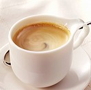 Espresso in a white cup with a nice curl in the foam on a white blank cloth.