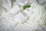 White baby shoes with blanket and hydrangea