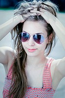 Grunge styled portrait of gorgoeus young brunette in sunlight, wearing sunglasses.
