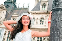 Beautiful young woman in a fashion pose in a historic Paris plaza with typical french architecture in the background.