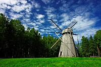 Old rural windmill on a meadow, surrounded by forest. High_contrast cloudscape.