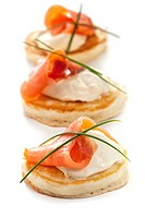 Blinis with smoked salmon and sour cream, garnished with chives.