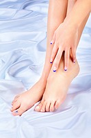 body part shot of beautiful healthy young woman´s hands and legs with manicured fingers and pedicured toes on silk cloth