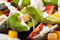 Fresh green salad with tomatoes croutons and creamy dressing.