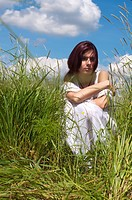 Portrait of the young beautiful woman. She is sitting in the grass