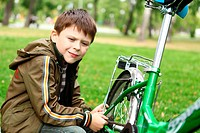 Happy smiling boy on a bicycle in the green park