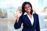 A pretty african american business woman signaling success at office