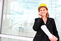A woman construction manager on a building site talking on phone.