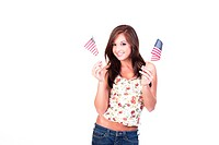 Fit teenage girl in blue jeans and flower print top, waving two small American flags, one in each hand.