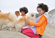 mixed race boy and girl on the sand petting some dogs
