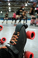 An abstract image of the roller_skates of a fallen skater as her teammates in the background continue to skate around the track of the roller derby.