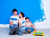 Happy young family with little son sitting near the wall with paintbrush