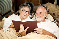 Senior couple reading together in the bed of their motor home.