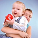 two brothers posing with an apple