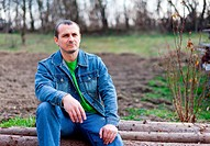 Portrait of a handsome young farmer sitting on a pile of logs, with ploughed land in background