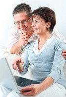 couple working with laptop at home