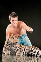 Young man with naked torso sits near to spotty leopard, on black background.