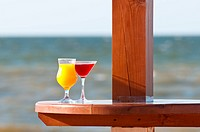 Orange cocktail on table, sea background