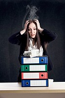 photo of young woman with binder pile holding her smoking head