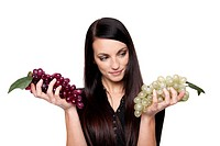 Isolated studio shot of a dark haired caucasian woman comparing a bunch of green grapes to a bunch of purple grapes.
