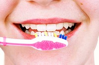 Close up of young woman perfect teeth about to clean them with pink tooth brush