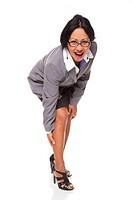 Isolated studio shot of a Latina businesswoman bending over and clutching her leg while looking at the camera.