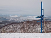 Views of the ski lift on a slope covered with forest from the mountain top
