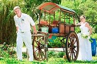 Funny bride and groom with cart outdoor