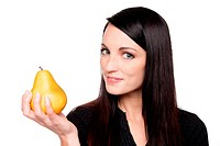 Isolated studio shot of a dark haired caucasian woman looking happily at a vibrant fresh pear.