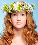 portrait of beautiful healthy redhead teen girl in garland on blue