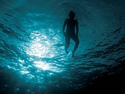 Child, in back_light, swim on the sea surface.