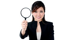 Portrait of a beautiful young businesswoman holding and looking at magnifying glass, over white background.