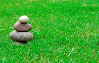 A balance group of zen stones on green grass.