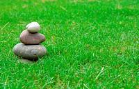 A balance group of zen stones on green grass.