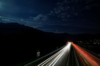 Car lights on a highway at night with moon light