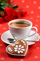 Gingerbread heart with coffee and red roses on red background. Shallow dof