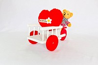 Red heart and bear on a tricycle.