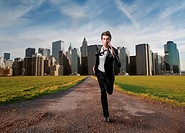 Young businessman running away from the city