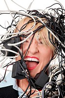 Mature businesswoman´s screaming in cables. Isolated on white background.