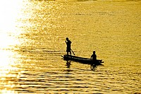 Two boys in a lonely boat, rowing toward the sunlight reflection
