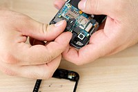 Clean Hands are repairing smartphone on the birch table.
