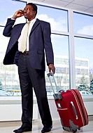African American business man stands with bag and phone in his hand