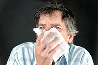 Close_up of a man sneezing into a tissue.