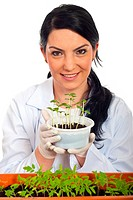 Happy scientist woman holding new cucumber plants in soil isolated on white background